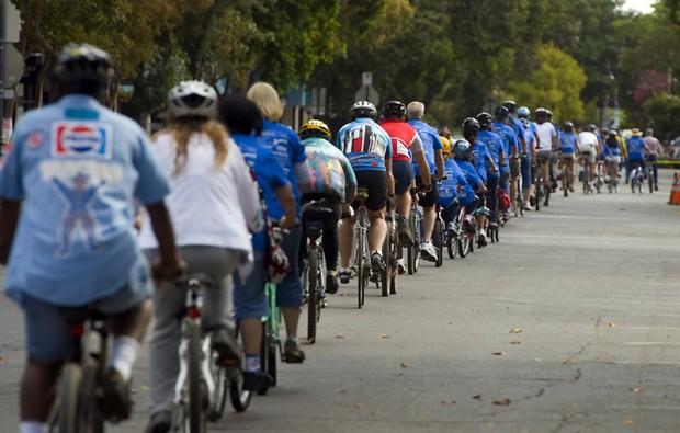 куча велосипедов и велосипедистов которые едут один за другим