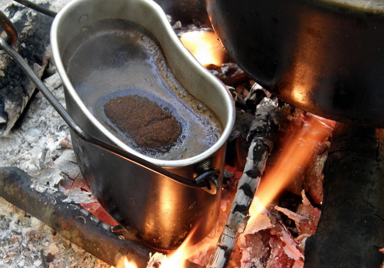 coffee being boiling in a pot on a fire