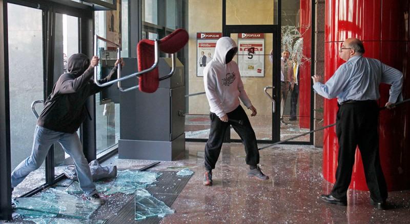 Клерк защищает помещение банка в Барселоне от вандалов во время массовых протестов против сокращения бюджетного финансирования в сфере образования