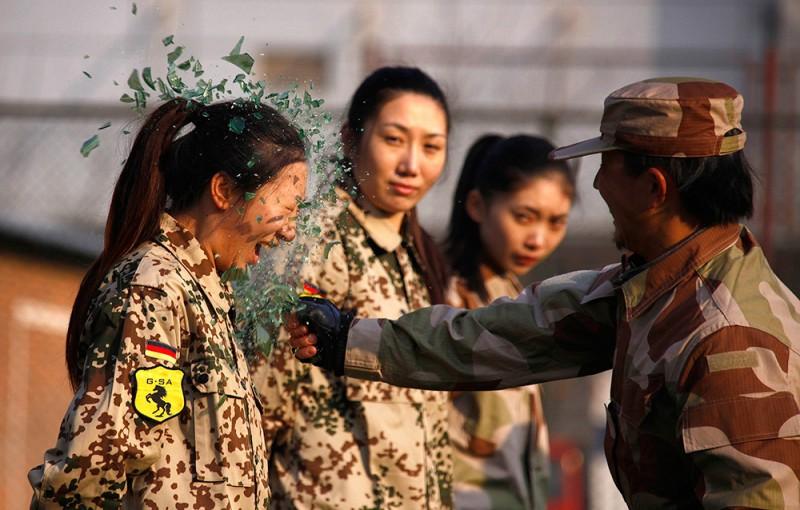 Инструктор разбивает бутылку о голову девушки-новобранца во время тренировки первых китайских девушек-телохранителей в Пекине