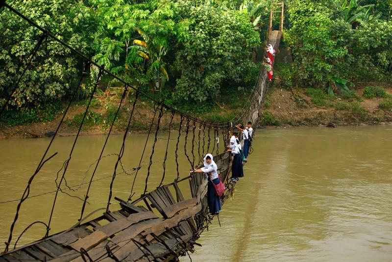 Школьники преодолевают подвесной мост, разрушенный вышедшей из берегов речкой Cиберанг в Индонезии