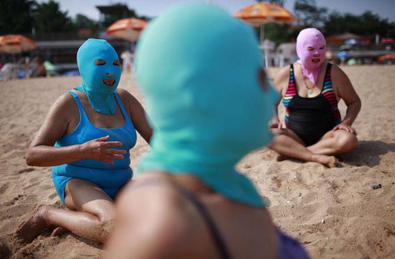 Китаянки на пляже защищают свои лица от ультрафиолета с помощью специальных нейлоновых масок. Они продаются во всех местных магазинчиках