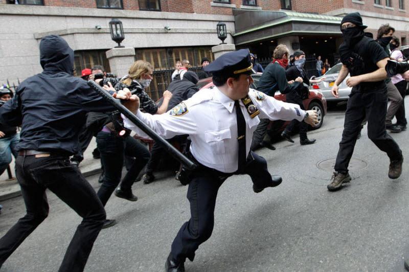 Полицейский разгоняет с помощью дубинки участников демонстрации