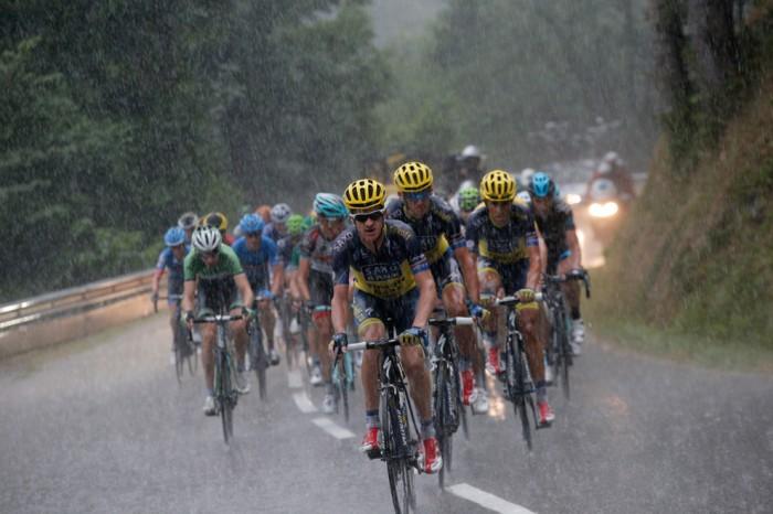 Пелотон с Майклом Роджерсом из Австралии, спереди, Роман Кройцигер из Чехии, на втором месте, Испанец Альберто Контадор - на третьей позиции, а Баук Моллема - из Нидерландов, в зеленом