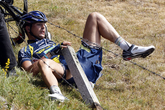 Падение на Тур де Франс Vacansoleil Hoogerland of Netherlands lies down after crashing during the ninth stage of the Tour de France 2011 cycling race