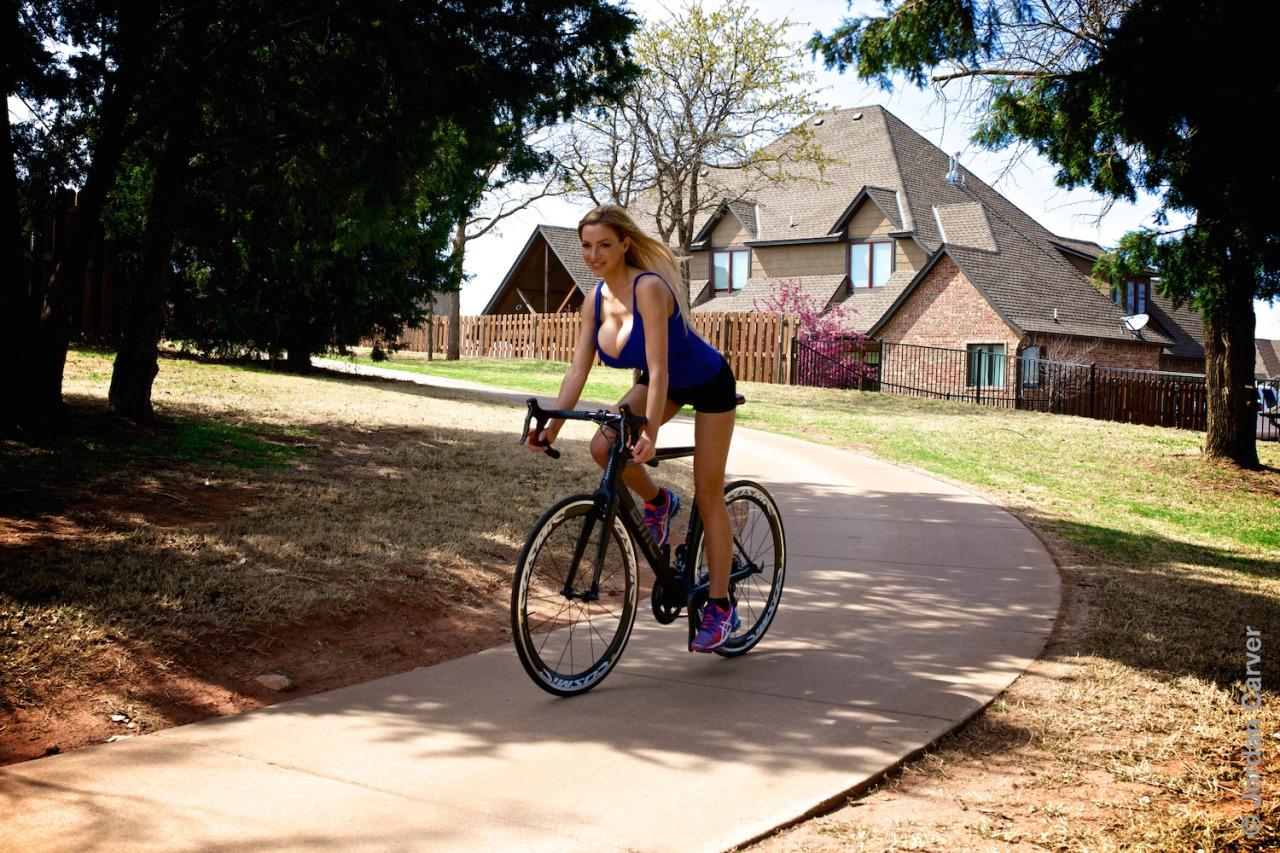 Девушка с большой грудью на шоссейном велосипеде